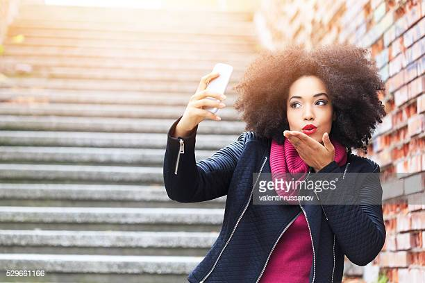 Beautiful young woman making selfie and sending air kiss