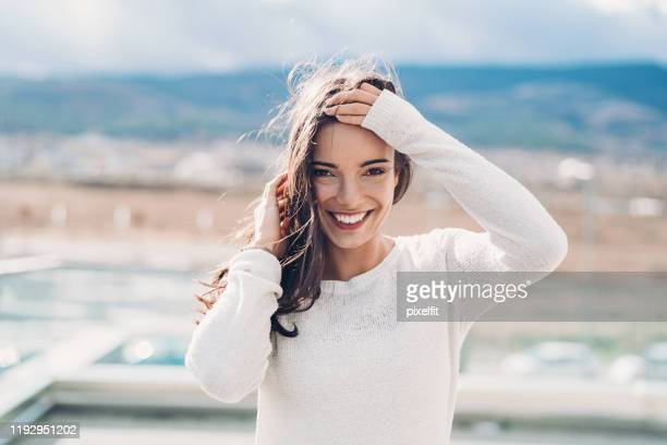 beautiful young woman on a windy day - hand in hair stock pictures, royalty-free photos & images