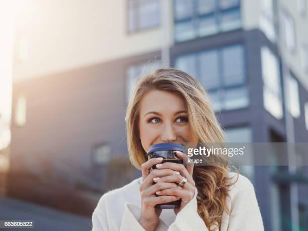 Schöne junge Frau in der Stadt Take away Kaffee trinken
