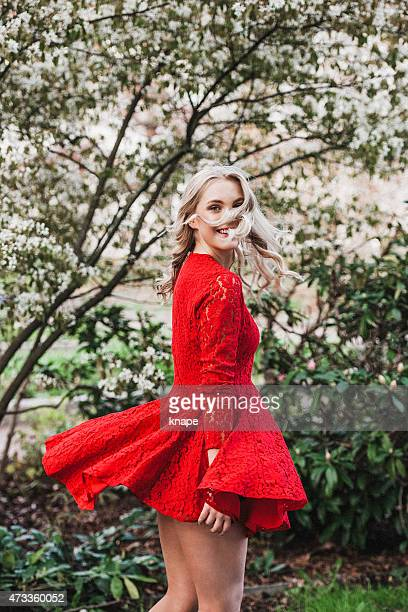 Beautiful young woman outdoors dancing dressed in red