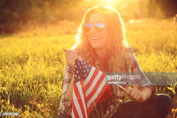 beautiful young woman outdoors with an American flag