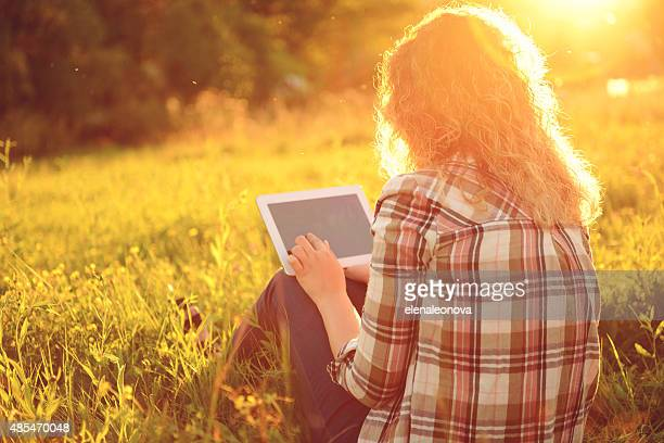 beautiful young woman outdoors with tablet PC
