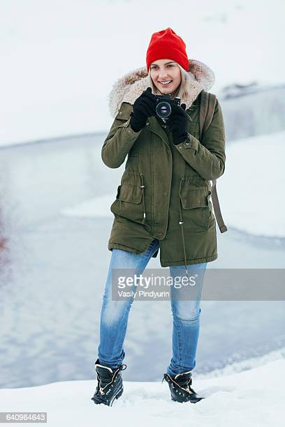 Beautiful young woman photographing through camera during winter