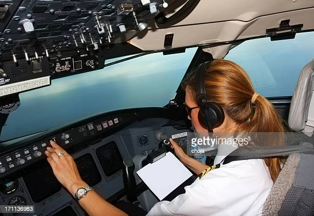 Beautiful young woman pilot at work