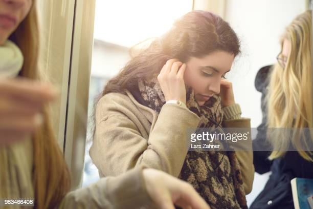 beautiful young woman placing earphones - homofobia fotografías e imágenes de stock