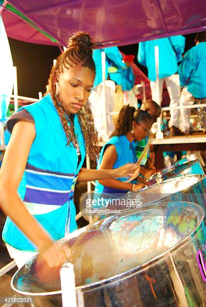 beautiful young woman playing a steel drum - steel drum stock photos and pictures