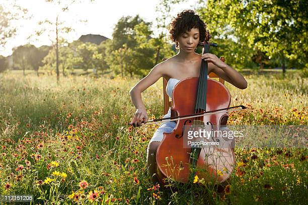 Beautiful young woman playing cello in a wildflower field