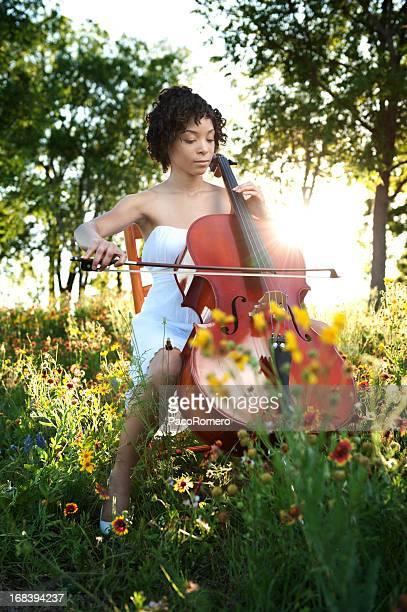Belle jeune femme jouant violoncelle dans la nature
