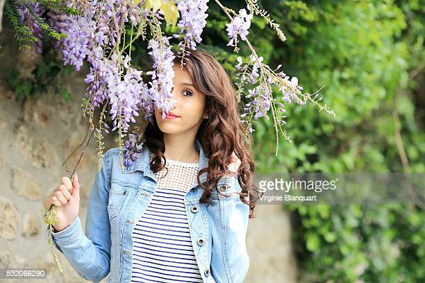beautiful young woman playing hide and seek with wisteria purple flowers - glycine photos et images de collection