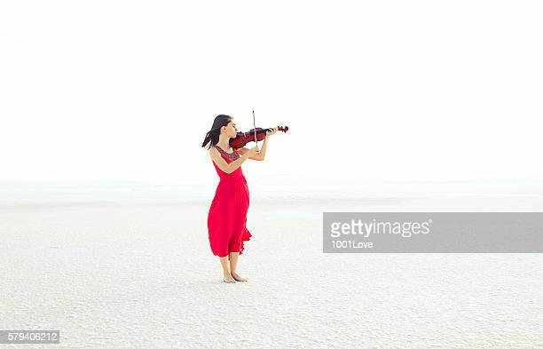 Beautiful young woman playing violin on snow