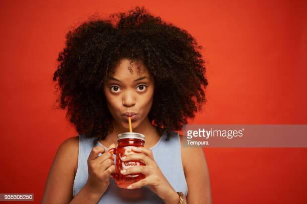 beautiful young woman portrait drinking a smoothie. - juice drink stock photos and pictures