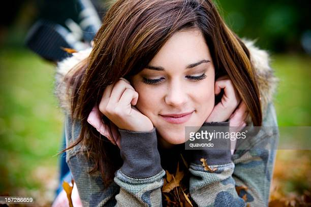 beautiful young woman portrait, lying on stomach in fall leaves - fur trim stock pictures, royalty-free photos & images