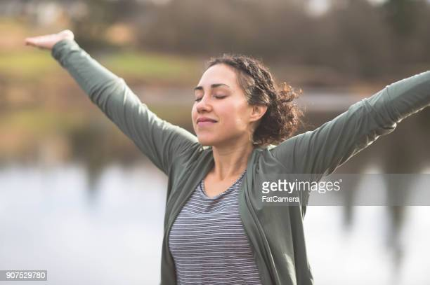 A Beautiful Young Ethnic Woman Practices Yoga By a Lake