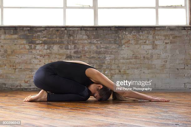 beautiful young woman practicing yoga - childs pose stock photos and pictures