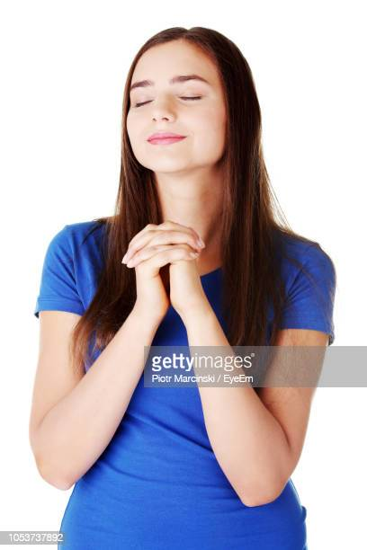 beautiful young woman praying against white background - 祈る ストックフォトと画像