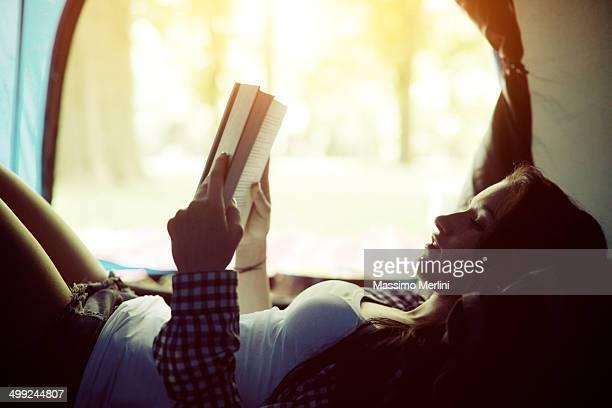 Belle jeune femme lisant un livre dans une tente