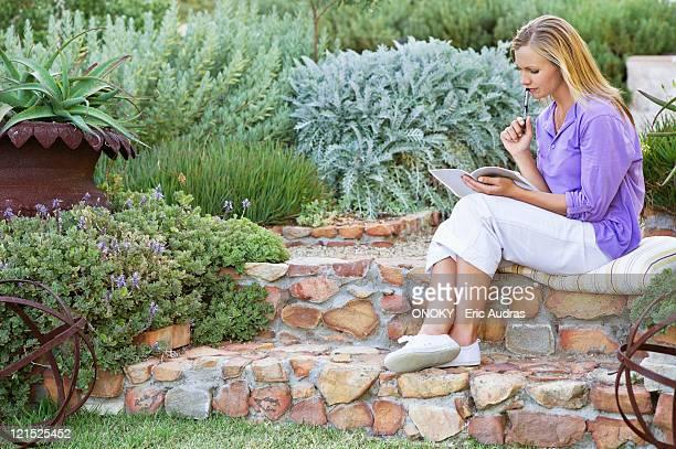 beautiful young woman reading book in garden - onoky stock-fotos und bilder