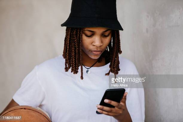 beautiful young woman reading her phone with basketball under arm - gender role fotografías e imágenes de stock