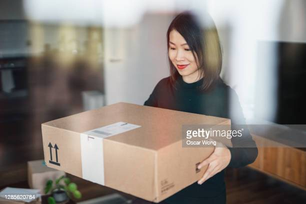 beautiful young woman receiving package at home - national holiday stock pictures, royalty-free photos & images