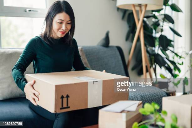 beautiful young woman receiving package at home - gift stock pictures, royalty-free photos & images