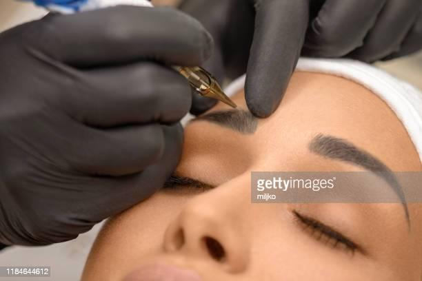 美麗的年輕女子接受永久化妝 - 眼眉 個照片及圖片檔