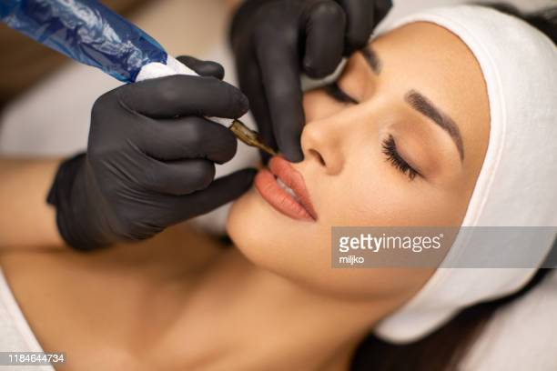 beautiful young woman receiving permanent make up - human lips stock pictures, royalty-free photos & images