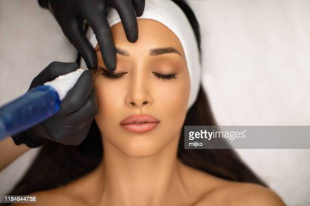 beautiful young woman receiving permanent make up - eye liner stock pictures, royalty-free photos & images