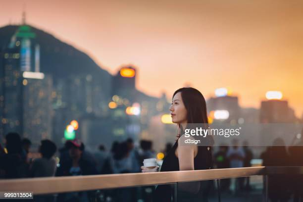 Beautiful young woman relaxing by the promenade drinking coffee and watching over sunset against cityscape