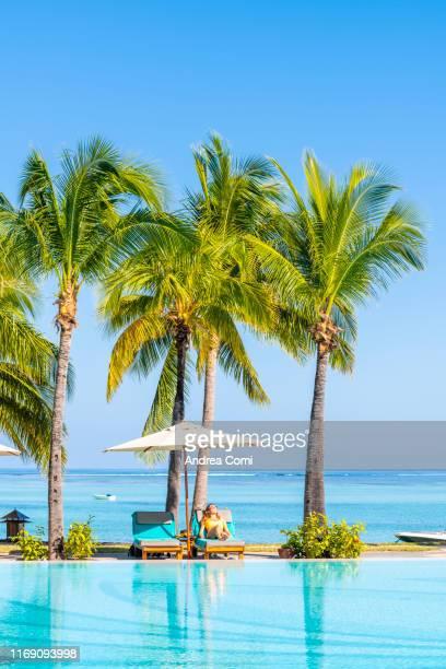 beautiful young woman relaxing in a swimming pool near the indian ocean - islas mauricio fotografías e imágenes de stock