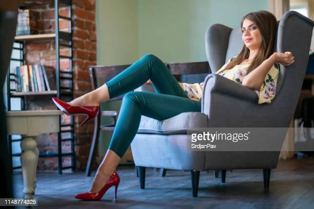 schöne junge frau entspannt sich im sessel - pumps stock-fotos und bilder