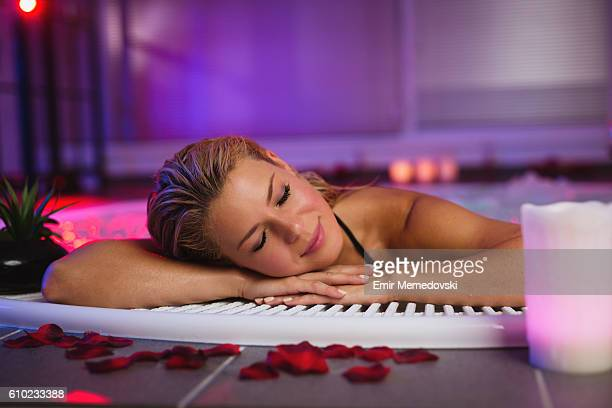 Beautiful young woman relaxing in jacuzzi at health spa.