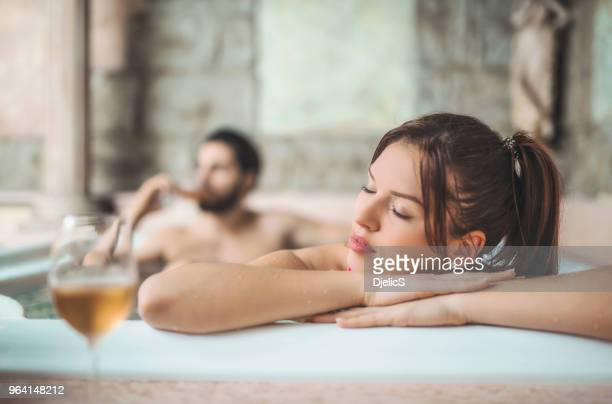 beautiful young woman relaxing in hot tub with her husband. - couple bathtub stock pictures, royalty-free photos & images