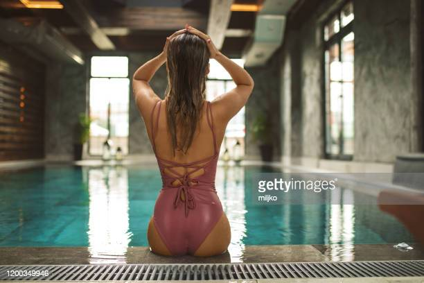 beautiful young woman relaxing on indoors poolside - one young woman only stock pictures, royalty-free photos & images