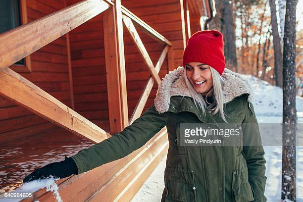 Beautiful young woman removing snow from railing