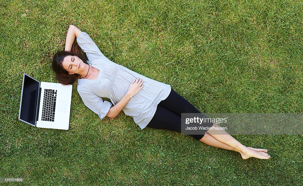 Caucasian Woman Laying In Grass Reading Book High-Res