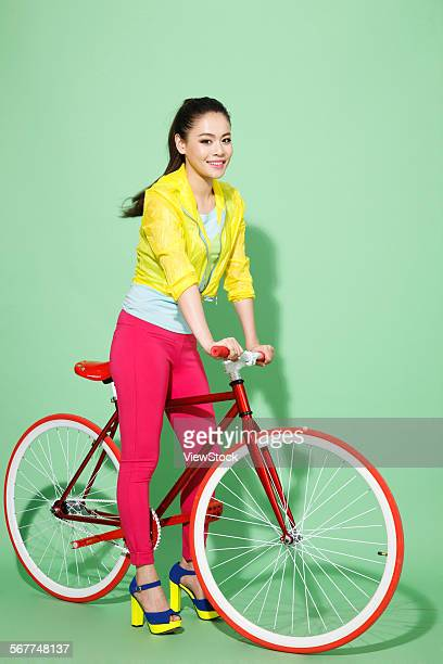 A beautiful young woman riding a bicycle