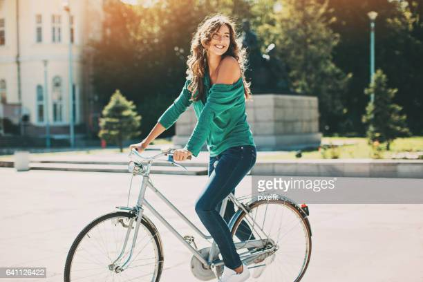 beautiful young woman riding a bike on a sunny day - bicycle stock pictures, royalty-free photos & images