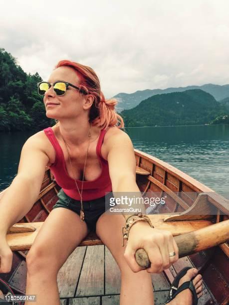 schönes junges frauenrudern auf einem holzboot - nur erwachsene stock-fotos und bilder