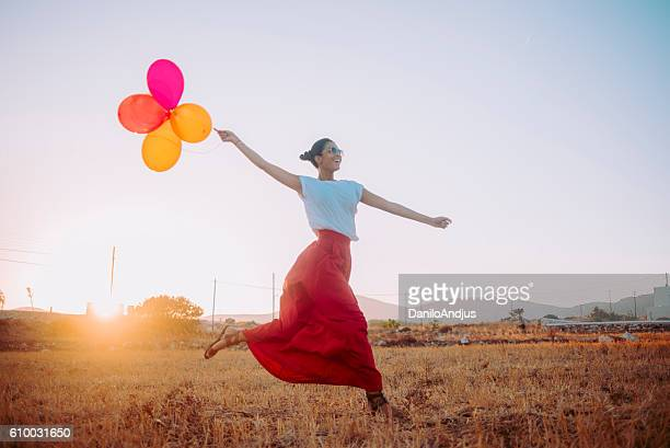 beautiful young woman running threw the field holding balloons