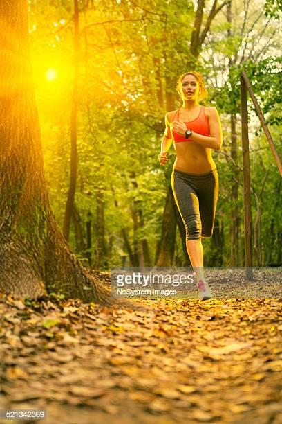 Belle jeune femme en train de courir dans le parc