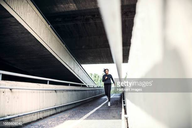 A beautiful young woman running under the bridge outdoors in the city.