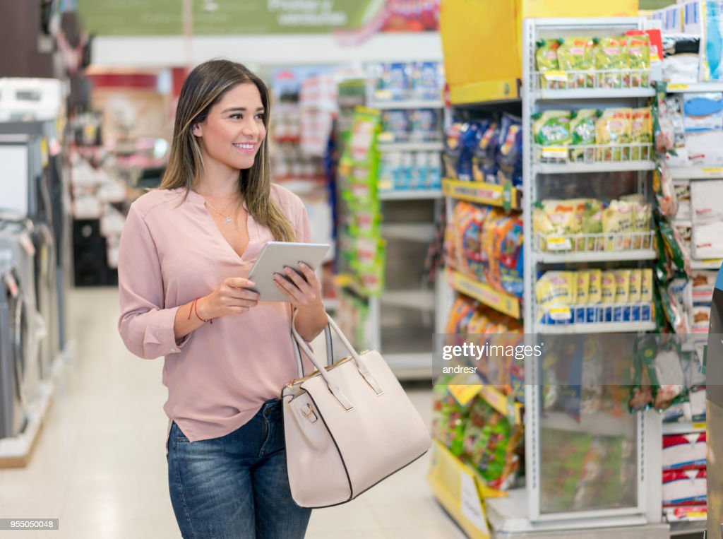Beautiful young woman shopping for groceries at the supermarket and holding a tablet to look at the shopping list : Stock Photo