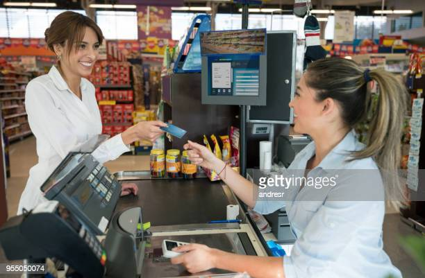 beautiful young woman shopping for groceries at the supermarket and paying the cashier with credit card both looking very happy - cashier stock pictures, royalty-free photos & images