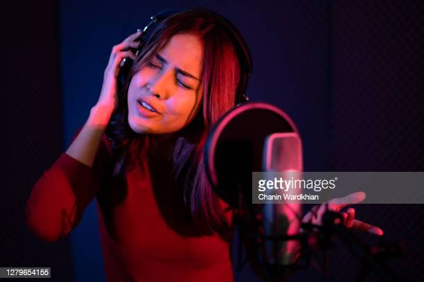 beautiful young woman singing behind the microphone at a recording studio and looking very happy - singer stock pictures, royalty-free photos & images
