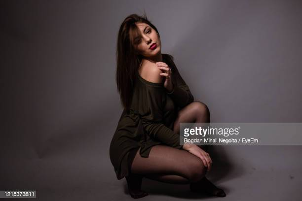 beautiful young woman sitting against gray background - bogdan negoita stock pictures, royalty-free photos & images