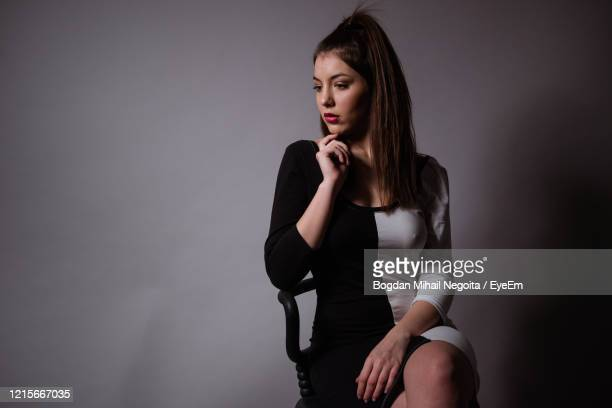 beautiful young woman sitting against wall - bogdan negoita stock pictures, royalty-free photos & images