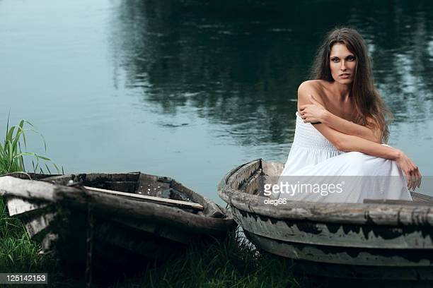 beautiful young woman sitting in a boat - hot women on boats stock pictures, royalty-free photos & images