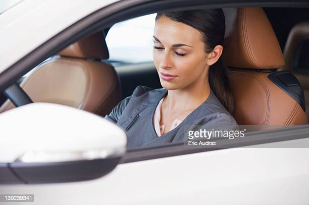 Beautiful young woman sitting in car with her eyes closed
