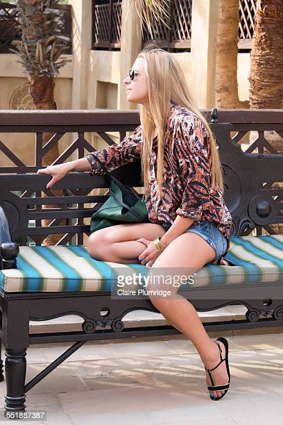 beautiful young woman sitting on a seat - claire plumridge stock pictures, royalty-free photos & images