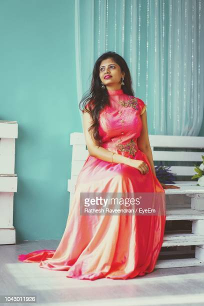 beautiful young woman sitting on bench at home - evening gown stock pictures, royalty-free photos & images
